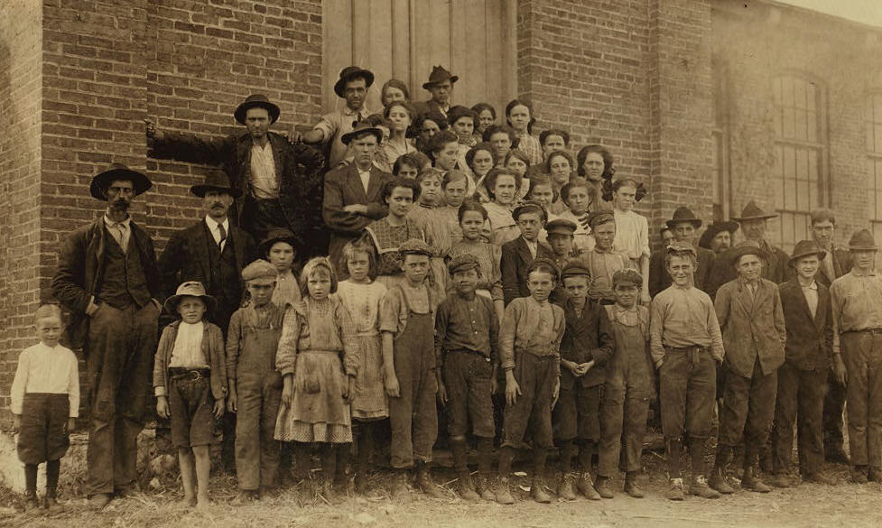 "The whole force in Elk Cotton Mills. Tiny boy in white waist on extreme left, ""Just helps his mother,"" the superintendent said. Next boy is Leo, with a ""steady job,"" Location: Fayetteville, Tennessee, November 1910, Lewis Hine."