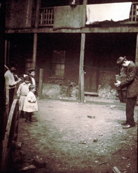 Lewis Hine taking picture near New York City tenement, 1910.