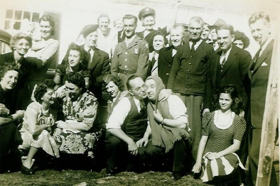 Odella (far left, in front of baby), Eglantine (kneeling below Odella, wearing light print dress), Mamie (top middle, wearing military hat), Henry (wearing sweater with tie), Frank (to Henry's left). Photo taken in 1944, in front of Henry's house at 4 Mill Circle.