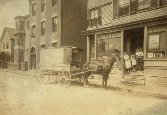 The wagon that delivers Home Work to Somerville, Mass. the owner of wagon (who is not the driver) is O.H. Brown, 27 Main Street, Reading Mass. These wagons (about 4 in all) are worked on commission, not owned by the factory. Location: Somerville, Massachusetts, August 1912, Lewis Hine.