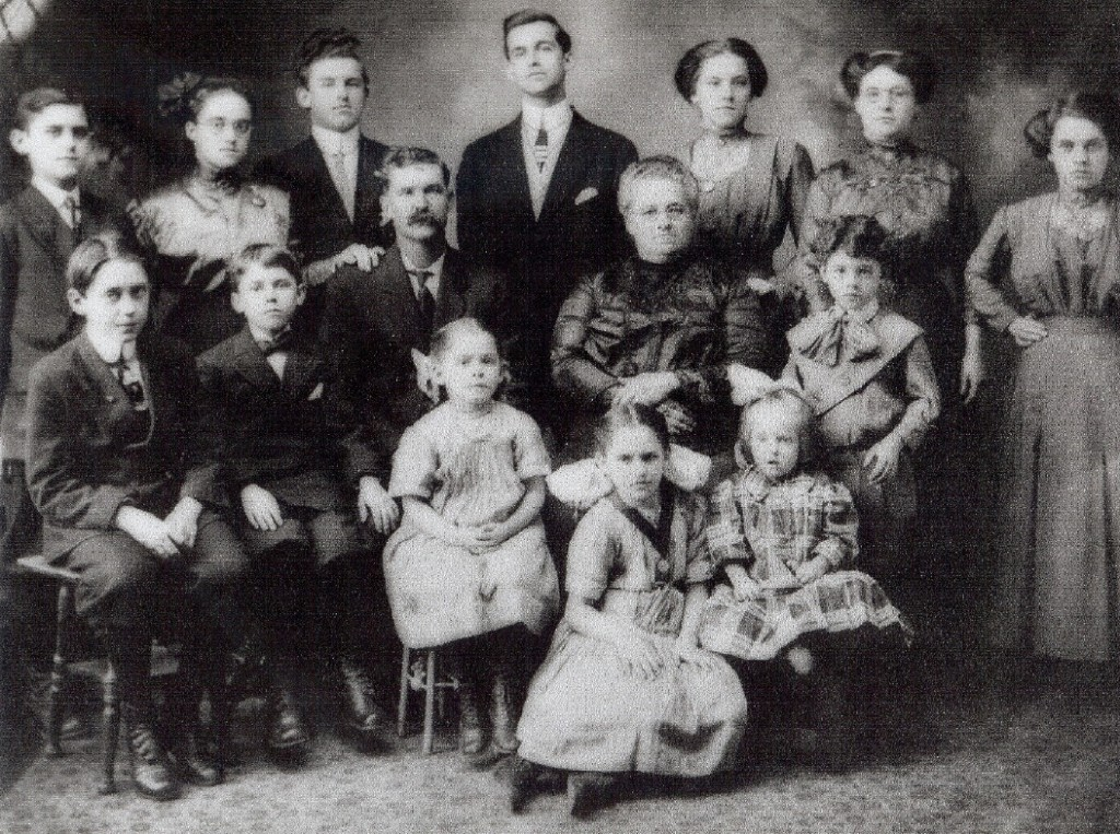 Top row (L-R): Adelard, Alma, Emile, Napoleon, Alexina, Elise, Rosanna. Second row (L-R): Omer, Norbert, Elie (father), Adele (mother), Amedee. Bottom row (L-R): Leocadie, Malvina, Irene.