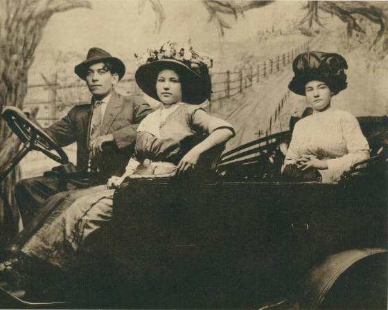 Mattie Young Ricks and Nelson Ricks with friend in back seat. Staged backdrop, circa 1918.