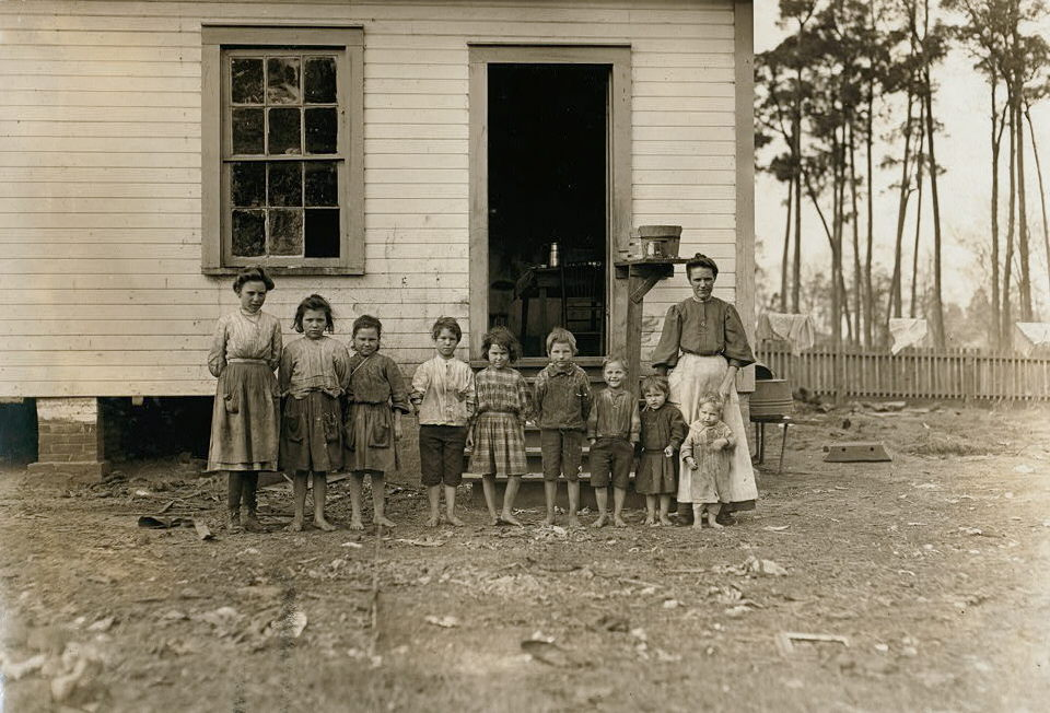 A family working in the Tifton (Ga.) Cotton Mill. Mrs. A.J. Young works in mill and at home. Nell (oldest girl) alternates in mill with mother. Mammy (next girl) runs 2 sides. Mary (next) runs 1 1/2 sides. Elic (oldest boy) works regularly. Eddie (next girl) helps in mill, sticks on bobbins. Four smallest children not working yet. The mother said she earns $4.50 a week and all the children earn $4.50 a week. Husband died and left her with 11 children. 2 of them went off and got married. The family left the farm 2 years ago to work in the mill. January 22, 1909. Location: Tifton, Georgia. Photo by Lewis Hine.