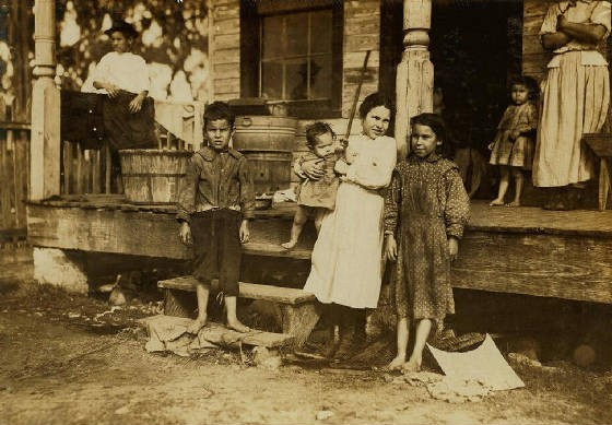 Alma Alves (on porch), with her family, Biloxi, Mississippi, February 1911. Photo by Lewis Hine.